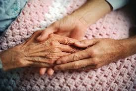 Senior and caregiver holding hands